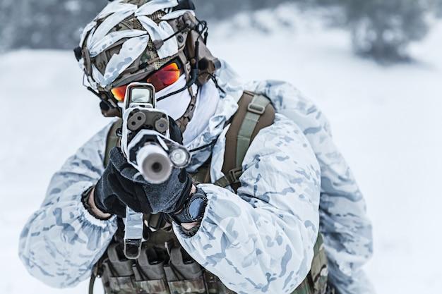 Guerra das montanhas árticas de inverno. ação em condições de frio. soldado com armas na floresta em algum lugar acima do círculo polar ártico, apontando para a câmera