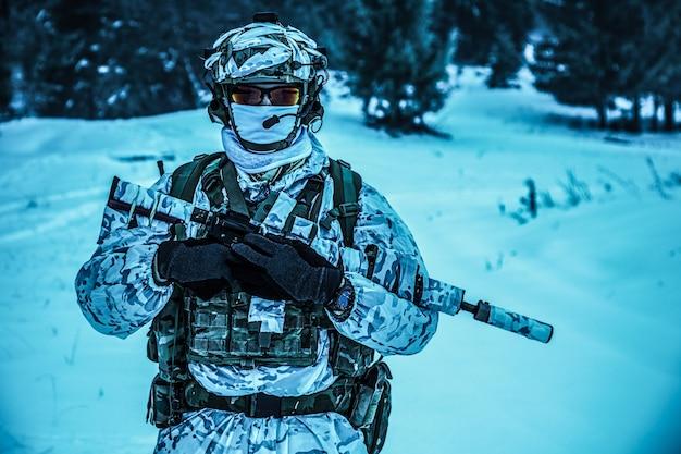 Guerra das montanhas árticas de inverno. ação em condições de frio. soldado com armas na floresta em algum lugar acima do círculo polar ártico