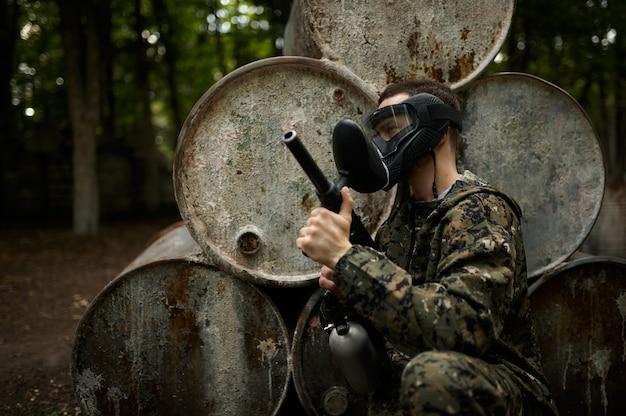 Guerreira feminina em máscara de camuflagem e proteção segura uma arma de paintball. esporte radical com arma pneumática e balas ou marcadores de tinta, jogo de equipe militar ao ar livre, táticas de combate