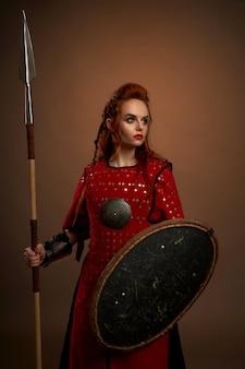 Guerreira, mantendo a lança e escudo e posando