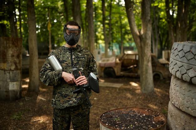 Guerreiro camuflado e máscara segura uma arma de paintball. esporte radical com arma pneumática e balas ou marcadores de tinta, jogo militar ao ar livre