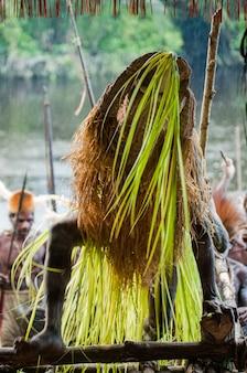 Guerreiro da tribo asmat disfarçado de espírito maligno está dançando uma dança ritual.