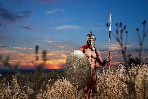 Guerreiro espartano no vestido de batalha com um escudo e uma lança