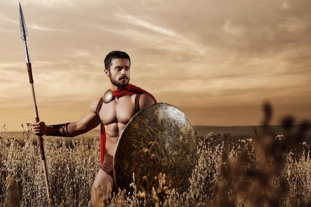 Guerreiro medieval musculoso em pé no campo