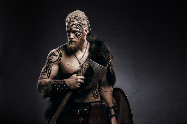 Guerreiro medieval viking com barba de tatuagem e tranças no cabelo com machado e escudo