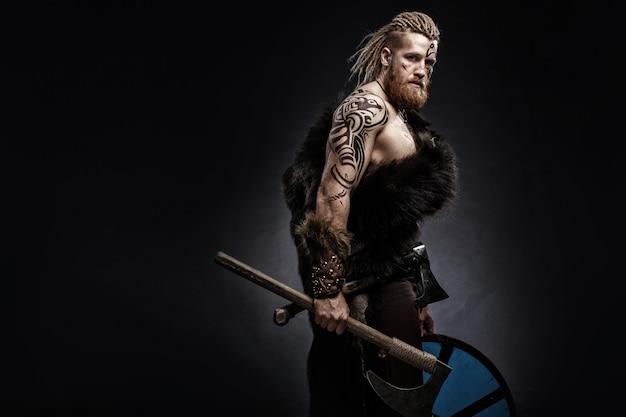 Guerreiro medieval viking vestido com pele de urso com tatuagem e machado