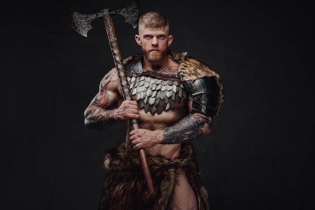 Guerreiro sério com corpo tatuado e musculoso, armadura leve e pele, segurando um machado de duas mãos no estúdio escuro