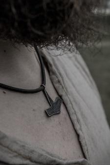 Guerreiro viking com cabelos cacheados, usando um colar de martelo