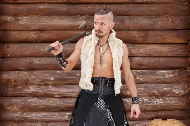 Guerreiro viking com um machado em um colete de pele perto de uma parede de madeira