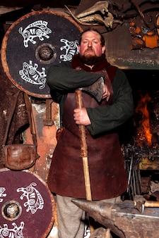 Guerreiro viking está perto do fogo em sua forja com armas nas mãos.