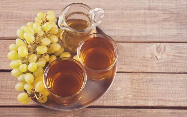 Gug e copos de suco de uva na velha mesa de madeira