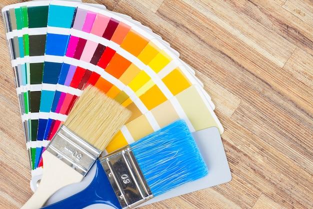 Guia de paleta de cores e pincéis na mesa de madeira