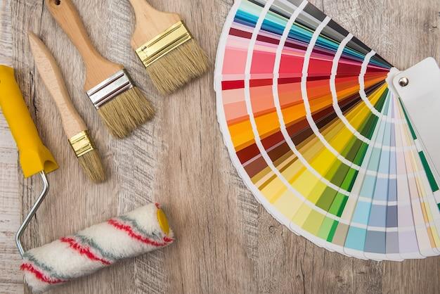 Guia de paleta de cores e rolo de pincel na placa de madeira