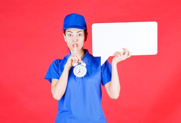 Guia feminino em uniforme azul, segurando uma placa de informações retangular branca com um despertador e pedindo silêncio.
