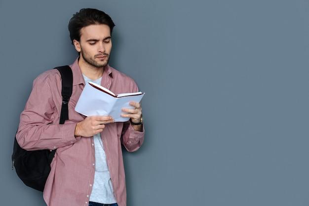Guia turístico. homem bonito e inteligente usando uma mochila e segurando um guia turístico enquanto o lê