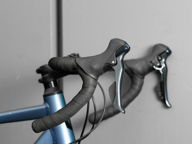 Guiador da bicicleta da estrada no fim cinzento da parede acima.