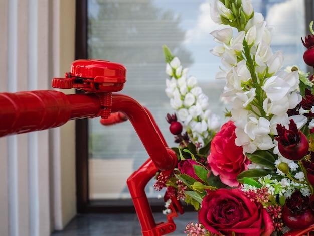 Guiador de bicicleta e cesta com flores. lindas flores artificiais na cesta de bicicleta