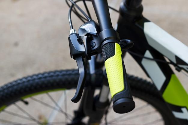 Guidão de bicicleta com apertos verdes no fundo da rua
