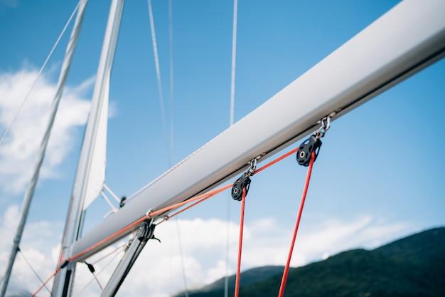 Guinchos com cordas vermelhas em um mastro branco de um iate à vela contra um céu azul brilhante