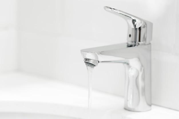 Guindaste chrome no lavatório de cerâmica no banheiro