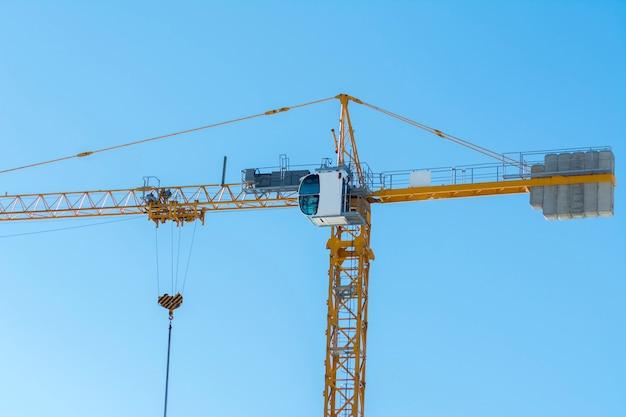 Guindaste de construção amarelo no fundo do céu azul