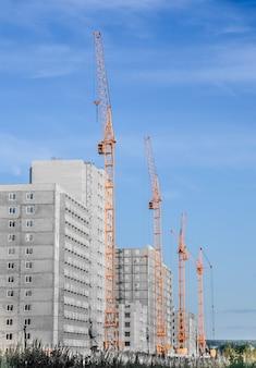 Guindaste de construção e prédio em construção contra céu nublado