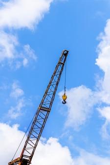 Guindaste de construção em um fundo de céu azul com nuvens brancas
