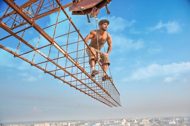 Guindaste de construção segurando a construção com o homem no alto