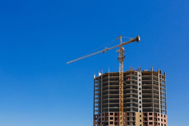 Guindaste de construção. um prédio alto está em construção contra um céu azul. indústria e indústria de construção