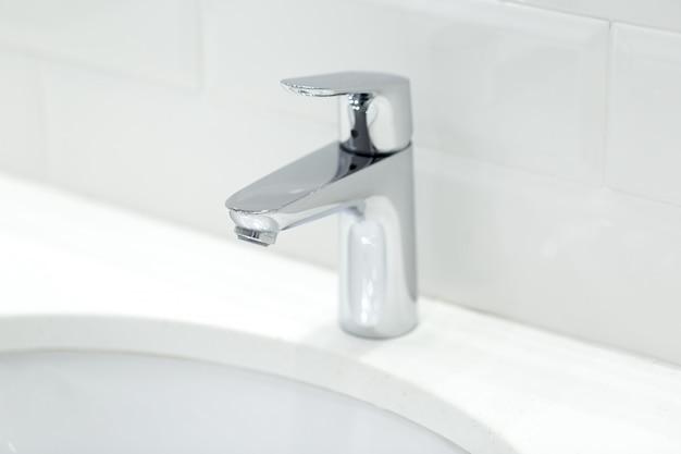 Guindaste de cromo no lavatório cerâmico no banheiro close-up