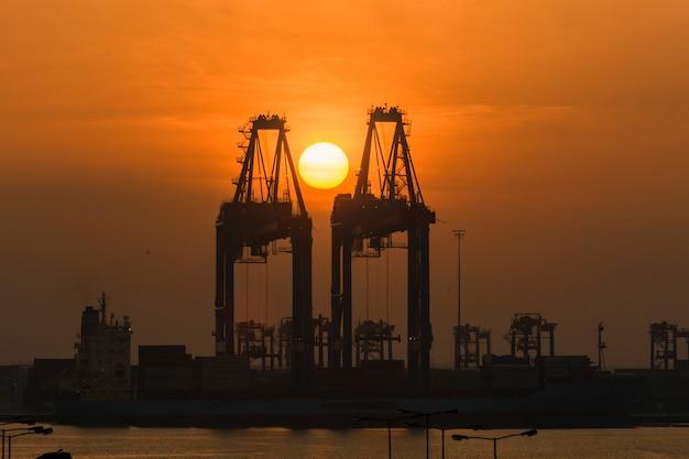 Guindaste de pórtico com sol do nascer do sol. manhã no porto.