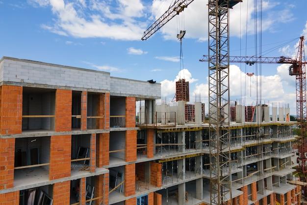 Guindaste de torre em alto edifício residencial de concreto em construção. conceito de desenvolvimento imobiliário.