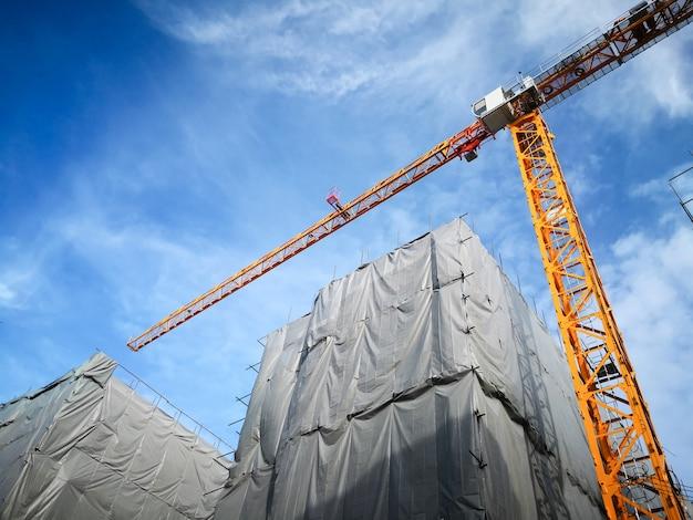 Guindaste de torre na visão de baixo ângulo do canteiro de obras de construção civil.
