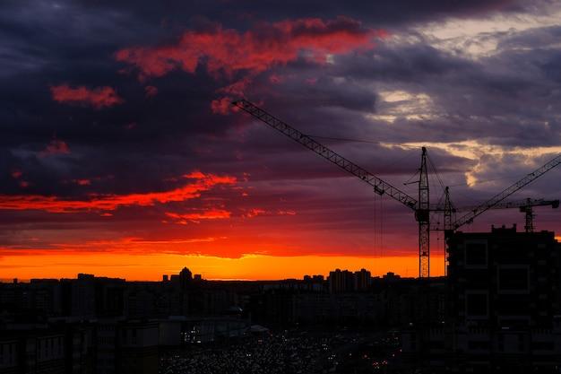 Guindaste de torre, novos edifícios, estacionamento e carros à distância durante o pôr do sol da cidade, contra o céu. cidade linda noite. área residencial com casas em construção.