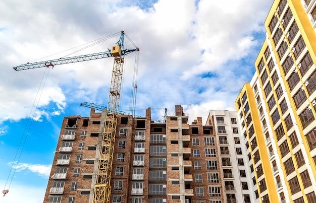 Guindaste e construção alta da elevação em construção contra o céu azul. cena de arquitetura moderna