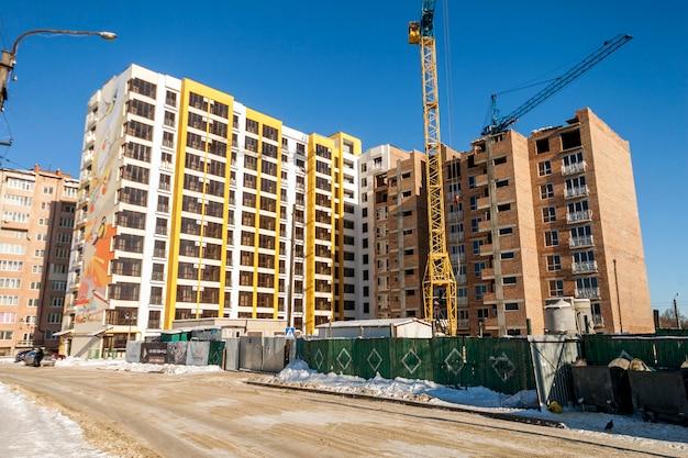 Guindaste e construção alta da elevação em construção contra o céu azul. fundo de arquitetura moderna