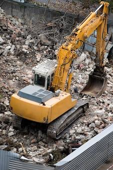Guindaste e trator no canteiro de obras destruindo um edifício