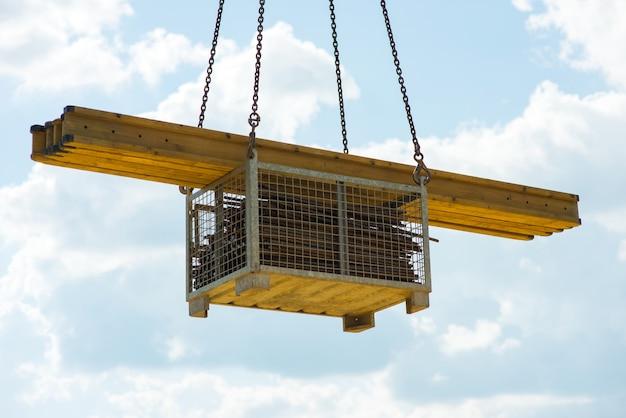 Guindaste levanta vigas de construção amarelas e reforço