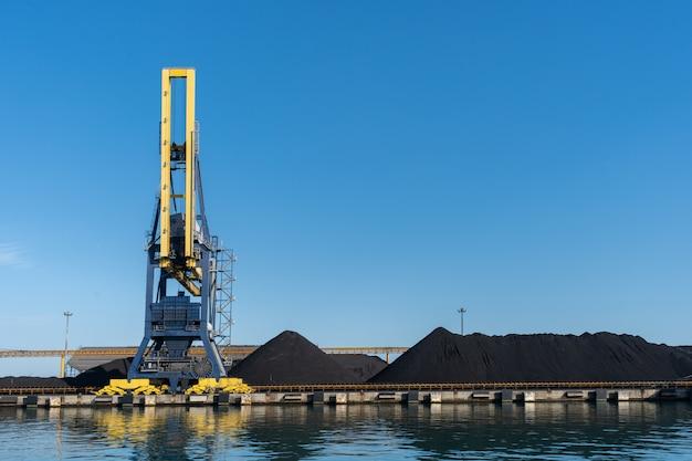 Guindaste portuário enorme cercado por carvão