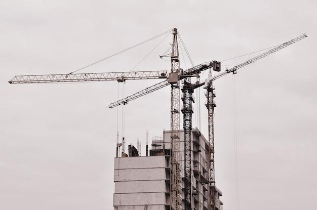 Guindastes altos de trabalho dentro do lugar para com construções altas sob a construção contra um céu azul claro.