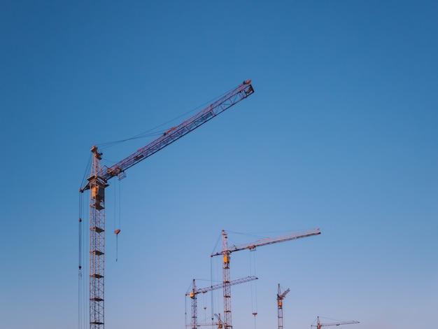 Guindastes de construção amarelos no céu azul