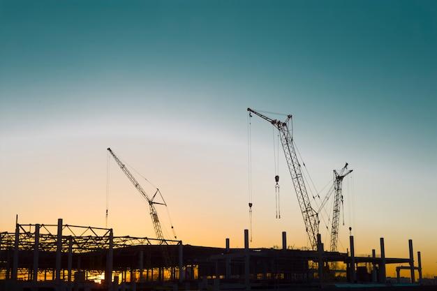 Guindastes de construção contra o pôr-do-sol.
