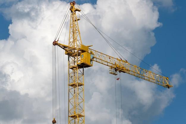 Guindastes de construção e construção de casa contra o céu azul