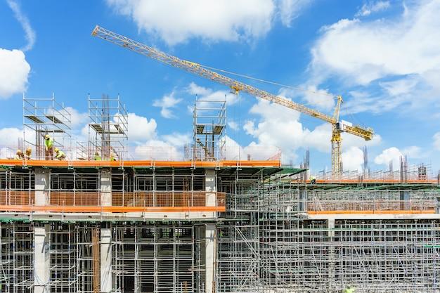 Guindastes de construção e prédio sob a construção contra o céu azul.