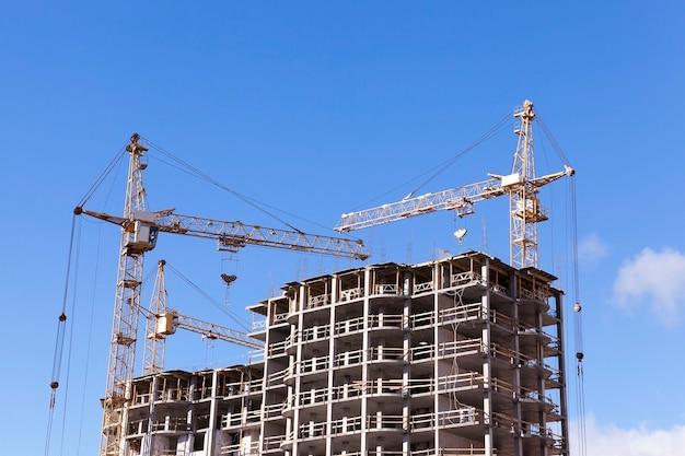 Guindastes de construção fotografados em close-up durante a construção de um novo prédio de apartamentos de vários andares, céu azul,