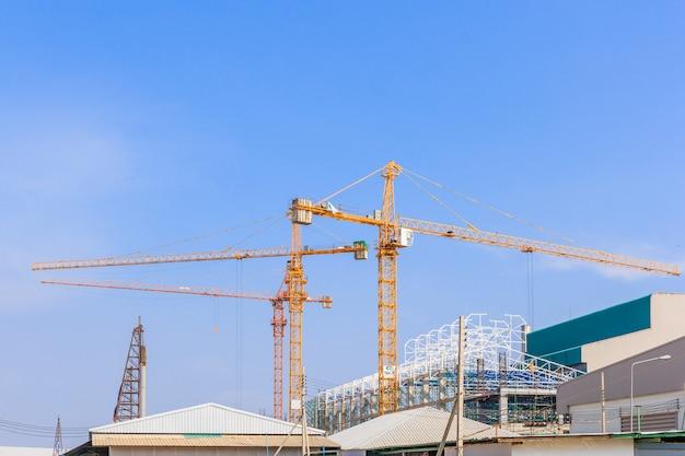 Guindastes de construção industrial e construção em um fundo lindo céu azul