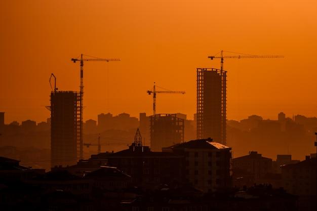 Guindastes de construção industrial e silhuetas de edifício ao pôr do sol