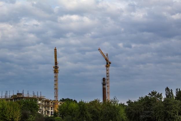 Guindastes de construção no céu nublado