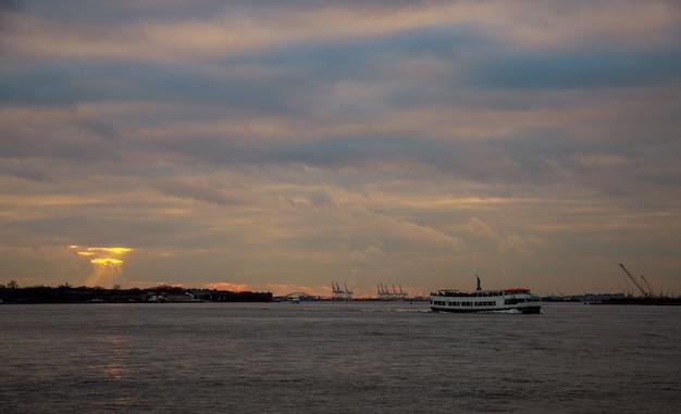 Guindastes de contêiner no porto de nova york ao pôr do sol e a estátua da liberdade