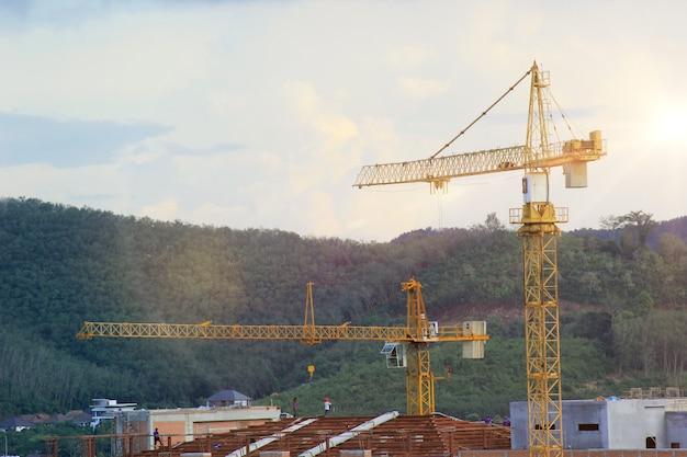 Guindastes de torre amarelos e alaranjados da construção das montanhas e do céu.